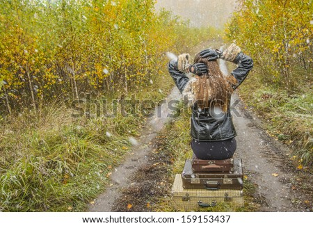 Young alone slim girl in a black leather jacket with fur collar sitting on the road in a forest in an old retro suitcase on snowy background of the autumn snowfall No face