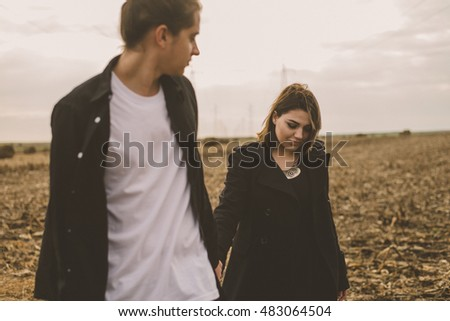Young alternative couple in love. Autumn Lovestory. Outdoors on a field.