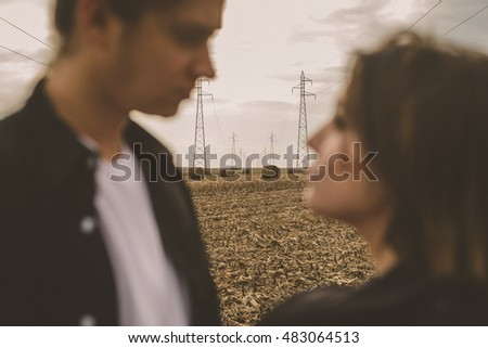 Young alternative couple in love. Autumn Lovestory. Outdoors on a field. Selective focus.
