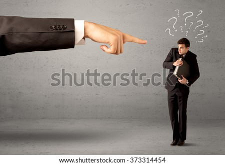 Young amateur confused businessman not understanding why he is getting fired concept with drawn question marks and large boss hand pointing at him - stock photo