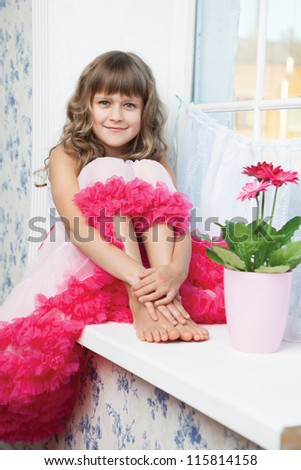Young amazing joyful girl teenager close-up dressed luxuriant wavy skirt with frill sitting with outstretched legs on white windowsill inside room near fresh natural flower in flowerpot - stock photo
