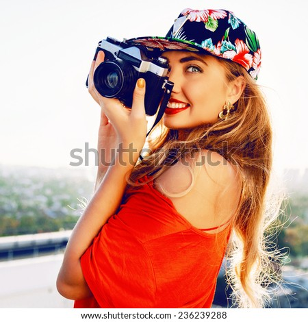 Young amazing pretty photographer woman traveling and taking pictures to her retro vintage camera from the roof. - stock photo