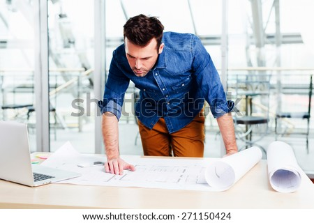 Young ambitious architect analyzing the details of his project - stock photo