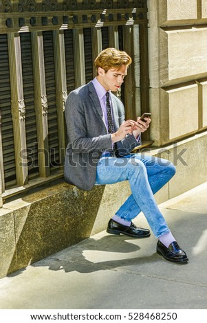 Young American business man travels, works in New York, wearing gray blazer, pink shirt, polka dot necktie, blue jeans, sitting on window frame on street, texting on cell phone. Color filtered effect.