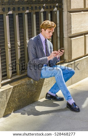 Young American business man travels, works in New York, wearing gray blazer, pink shirt, polka dot necktie, blue jeans, sitting on window frame on street, texting on cell phone.