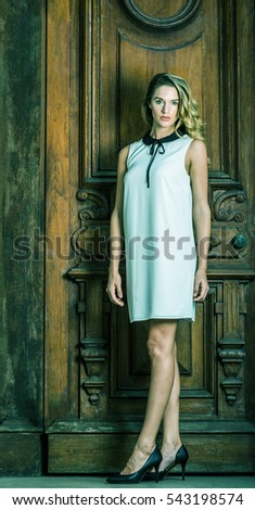 Young American Business Woman with long curly blonde hair in New York, wearing sleeveless white dress with black collar, high heels, standing by vintage style office door way. Color filtered effect