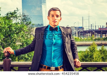 Young American Businessman, dressing in black blazer, blue shirt, bow tie, standing by railing on balcony, confident, successful. Modern business high building on background. Instagram filtered effect - stock photo