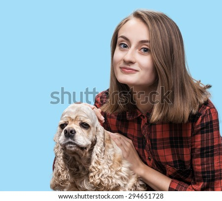 Young american cocker spaniel and beautiful woman on blue background with copy-space