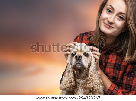 Young american cocker spaniel and beautiful woman on soft sunset sky background with copyspace