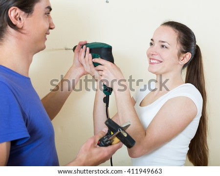 Young american couple drilling wall with drill at home