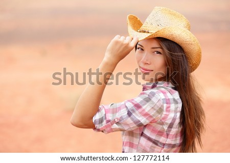 Young american cowgirl woman portrait outdoors. Beautiful natural woman saying hello looking at camera touching cowboy hat. Multicultural Caucasian / Asian girl in her twenties outdoor in nature. - stock photo