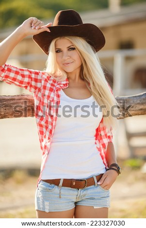 Young american cowgirl woman portrait outdoors. Beautiful natural woman saying hello looking at camera touching cowboy hat.  girl in her twenties outdoor in nature. - stock photo