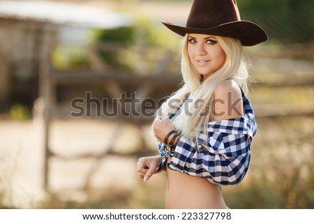 Young american cowgirl woman portrait outdoors. Beautiful natural woman saying hello looking at camera wearing cowboy hat. girl in her twenties outdoor in nature. - stock photo