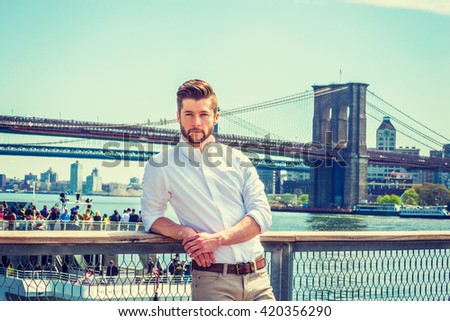 Young American man with beard traveling in New York, wearing white shirt, standing by fence at harbor, looking around, thinking. Manhattan, Brooklyn bridges, boat with many people on background.  - stock photo