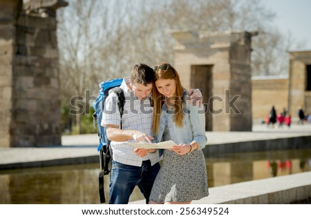 young American student and tourist couple visiting Egyptian monument reading city map carrying expedition backpack in holiday tourism and vacation travel concept - stock photo
