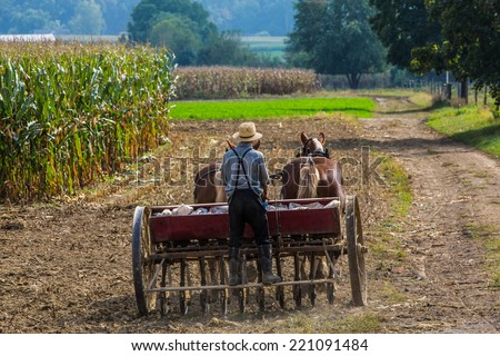 Young amish farmer sowing a field during the fall season. - stock photo