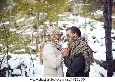 Young amorous couple celebrating Valentine�¢??s day in winter forest