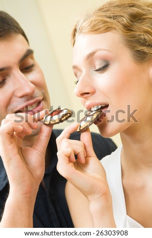 Young amorous couple eating cookies together at home - stock photo