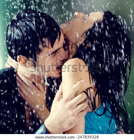 Young amorous couple hugging and kissing under a rain, outdoors - stock photo
