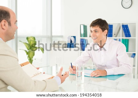 Young and adult businessmen discussing project - stock photo