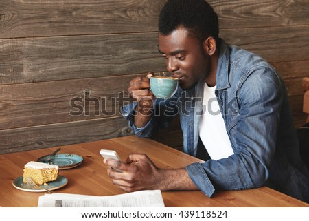 Young and attractive African man in casual dress typing messages in social networks and smiling. He looks so positive and fresh on wooden background, ready to make a sip of fresh brewed coffee. - stock photo