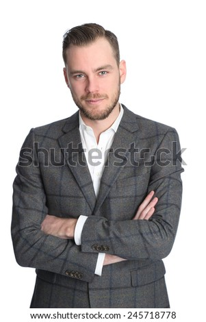 Young and attractive businessman standing against a white background wearing a grey jacket and white shirt. White background. - stock photo