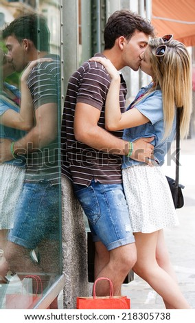 Young and attractive couple on holiday, kissing and embracing while shopping with paper bags, traveling in a destination city street, outdoors. Love, passion and relationships.