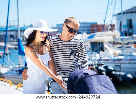 Young and attractive couple walking with a baby pram outdoor - stock photo