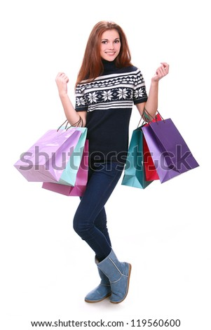 Young and attractive girl in sweater with shopping bags - stock photo