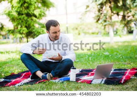 Young and attractive man relaxes in the park at lunch time