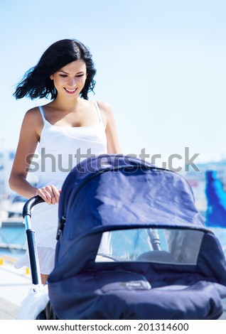 Young and attractive mother walking with a baby pram outdoor - stock photo