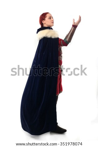 young and attractive red haired  female warrior,  wearing a red medieval tunic and leather Armour, velvet fur lined cloak.  isolated on a white background. - stock photo