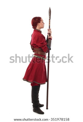 young and attractive red haired  female warrior,  wearing a red medieval tunic and leather Armour.  holding a spear as a weapon. side view. isolated on a white background. - stock photo