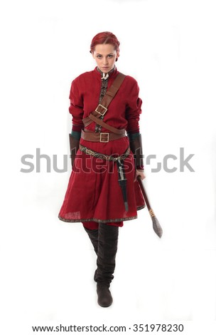 young and attractive red haired  female warrior,  wearing a red medieval tunic and leather Armour.  holding a spear as a weapon. walking towards camera isolated on a white background. - stock photo