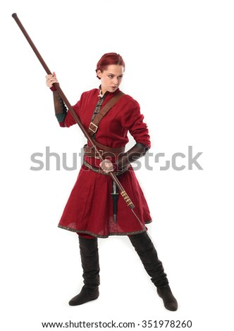 young and attractive red haired  female warrior,  wearing a red medieval tunic and leather Armour. holding a spear as a weapon.  isolated on a white background. - stock photo