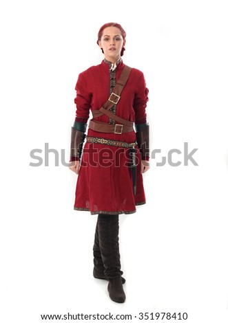 young and attractive red haired  female warrior,  wearing a red medieval tunic and leather Armour, walking towards camera. isolated on a white background. - stock photo