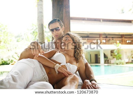 Young and attractive sexy couple lounging on a tropical garden bed in an exotic hotel spa garden, relaxing next to a swimming pool. - stock photo