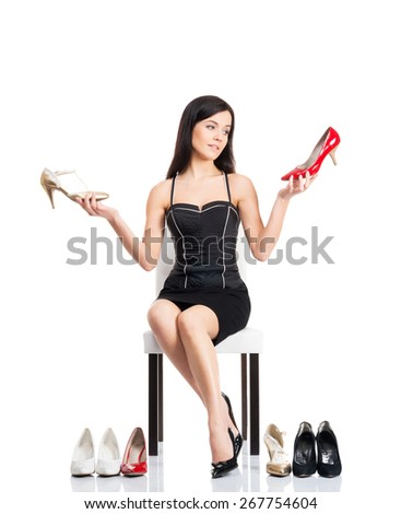 Young and attractive woman choosing shoes isolated on white - stock photo