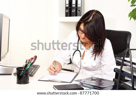 Young and attractive woman doctor in her office - stock photo
