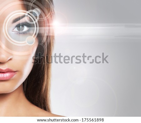 Young and attractive woman from future with a laser hologram on her eyes (ophthalmology and eye scanning technology concept). - stock photo