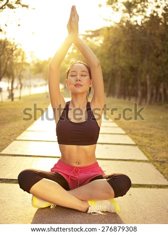 young and beautiful asian woman practicing yoga outdoors in park in the warm light of sunset, meditation, fitness, healthy life and lifestyle concept. - stock photo