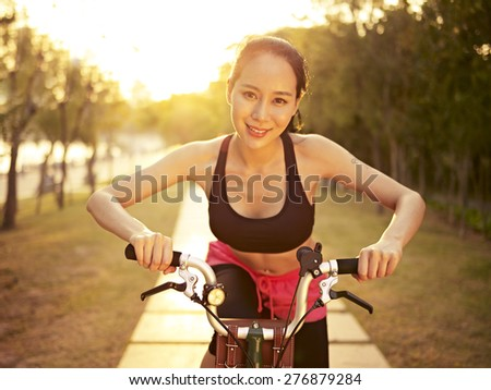 young and beautiful asian woman riding bicycle outdoors in park in warm sunlight, smiling and cheerful; fitness, sport and exercise, healthy life and lifestyle concept. - stock photo