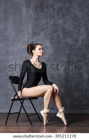 Young and beautiful ballerina sitting on a chair in a point shoes. - stock photo