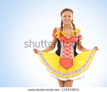 Young and beautiful bavarian girl over the blue background - stock photo