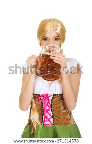 Young and beautiful bavarian woman drinking beer. - stock photo