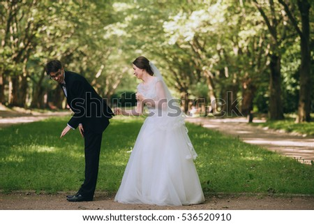 young and beautiful bride and groom having fun outdoors