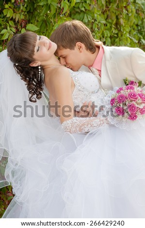 Young and beautiful bride and groom in the summer park - stock photo