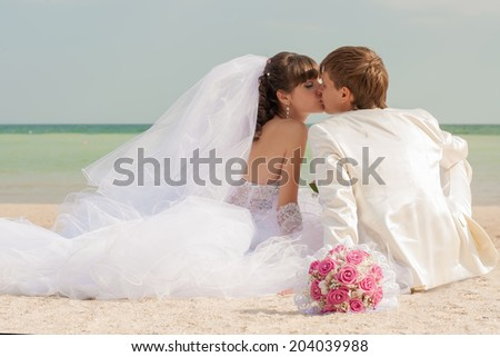Young and beautiful bride and groom on the beach in summer - stock photo