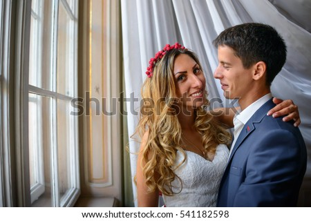 young and beautiful bride and groom standing near window