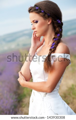 Young and beautiful bride in lavender field, wedding day in summer.  - stock photo